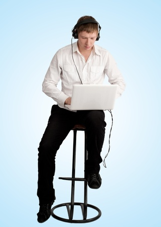 Young man with laptop listening to music at headphones, blue background photo