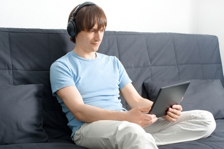 Young man working with a laptop and listening music on headphone  photo