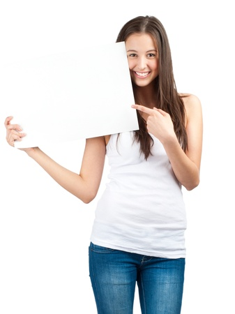a placard: Full length portrait of a happy young casual woman holding a blank signboard and pointing, isolated on white background Stock Photo