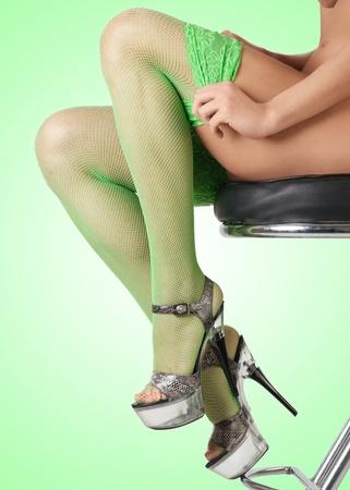 Female legs in green fishnet stockings against green background Stock Photo - 10845156