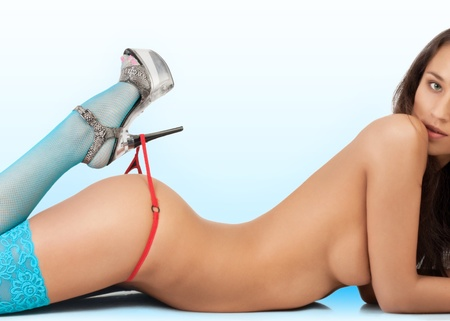 Close-up of legs and buttocks of a naked slim woman in sexy lingerie over blue background