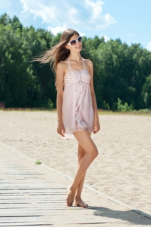 Young beautiful woman in summer dress and sunglasses on the beach Stock Photo - 10845111