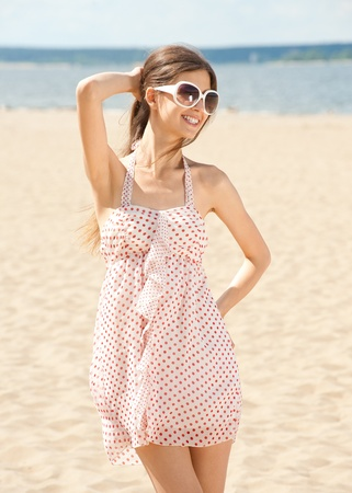 Young beautiful woman in summer dress and sunglasses on the beach  photo