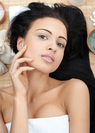 bare body women: Close-up portrait of young beautiful spa woman lying on bamboo mat at spa salon