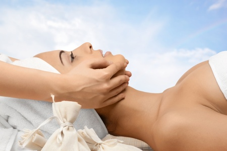 Close-up of a young beautiful woman getting spa treatment against blue sky. Facial massage.  photo