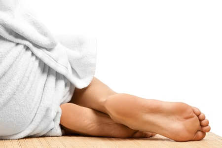 bare body women: Close-up of female feet at spa salon, isolated over white background
