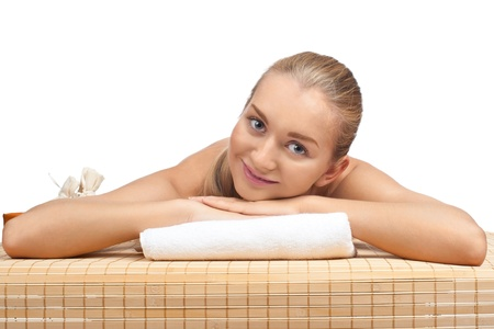 bare body women: Portrait of young beautiful spa woman lying on bamboo mat and smiling. Isolated on white background.