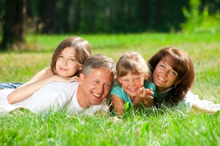 Happy caucasian family lying down on the grass in park photo