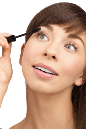 Beautiful woman applying mascara on her eyelashes, isolated on white background photo