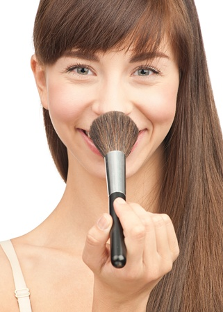 Close-up portrait of pretty young woman with brush for makeup, isolated on white photo