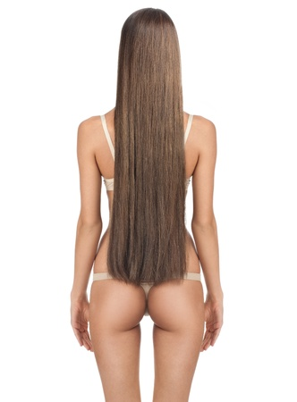 Rear view of beautiful woman with long straight brown hair and slim body. Isolated on white background photo