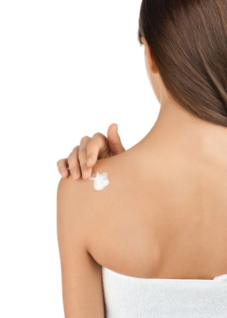 Rear view of young beautiful woman wearing towel applying moisturizer cream on her back photo