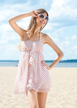 young girl barefoot: Young beautiful woman in summer dress and sunglasses on the beach
