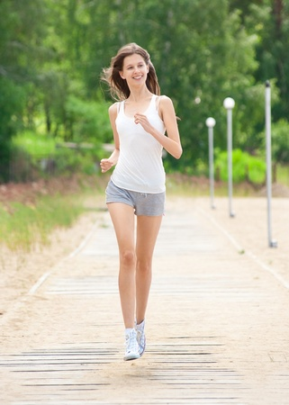 Happy young woman running outdoors in park  photo