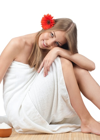 Young beautiful spa woman with flower in her hair sitting on bamboo mat at spa salon Stock Photo - 10844905