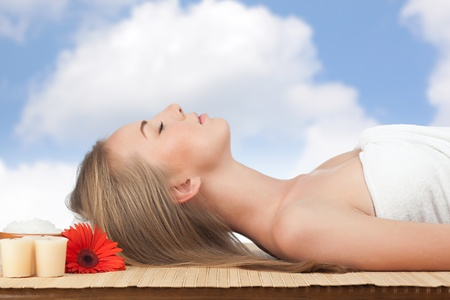 Portrait of young beautiful spa woman with flower lying on bamboo mat against sky Stock Photo - 10844770