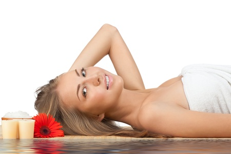 Portrait of young beautiful spa woman with flower in her hair lying on bamboo mat in water Stock Photo - 10844642