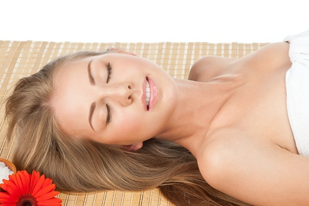 Portrait of young beautiful spa woman with flower lying on bamboo mat at spa salon Stock Photo - 10845066