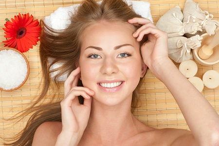 Portrait of young beautiful spa woman with flower lying on bamboo mat at spa salon photo