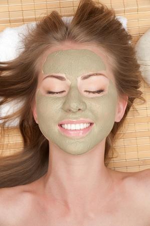 pulizia viso: Close-up di giovane donna bellissima con maschera all'argilla facciale al salone della stazione termale