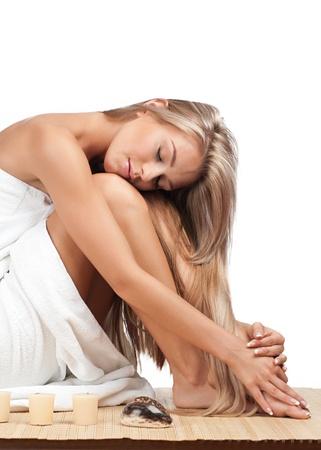 peluqueria y spa: Retrato de mujer hermosa joven que llevaba una toalla y sentarse en estera de bamb� en el sal�n de spa Foto de archivo