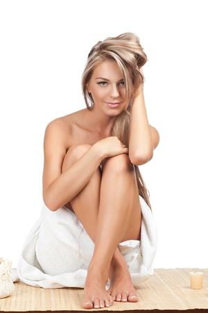 Portrait of young beautiful woman wearing towel and sitting on bamboo mat at spa salon Stock Photo - 10844661