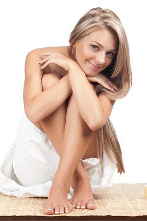 Portrait of young beautiful woman wearing towel and sitting on bamboo mat at spa salon photo