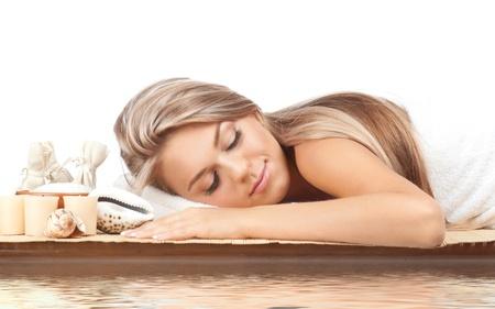 mimos: Retrato de mujer joven y hermoso balneario con los ojos cerrados tumbado en la estera de bambú en agua