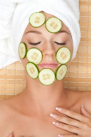 resting mask: Young beautiful woman with facial mask of cucumber on her face lying at spa salon