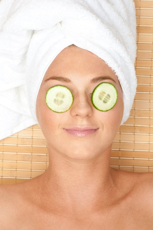 closed eye: Young beautiful woman with facial mask of cucumber on her face lying at spa salon