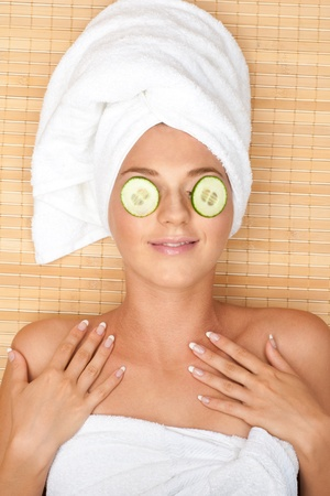 Young beautiful woman with facial mask of cucumber on her face lying at spa salon photo