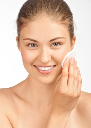 Portrait of young beautiful woman with cotton swab cleaning her face photo