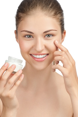 Portrait of young beautiful woman applying moisturizer cream on her face, isolated on white background Stock Photo - 10844898