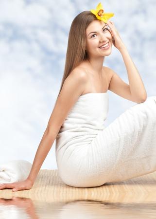 Portrait of young beautiful spa woman sitting on bamboo mat against blue sky and water photo