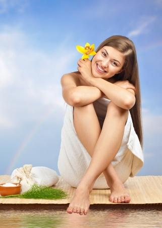 gezondheid: Portret van jonge mooie spa vrouw zit op bamboe mat tegen de blauwe lucht en water Stockfoto