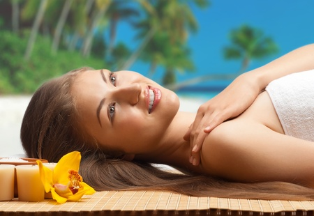 Close-up portrait of young beautiful spa woman lying on the beach