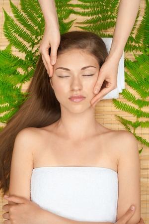 ojos cerrados: Retrato de una mujer hermosa joven que recibe masaje facial en el salón de spa