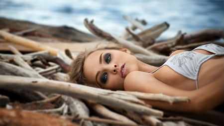 Fashion shot of a young beautiful woman in white swimsuit on the beach