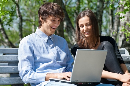 Young couple sitting together on park bench and using laptop photo