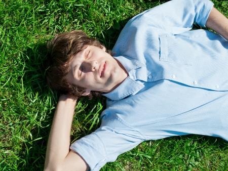so�ando: Apuesto joven tumbado en el c�sped y relajante