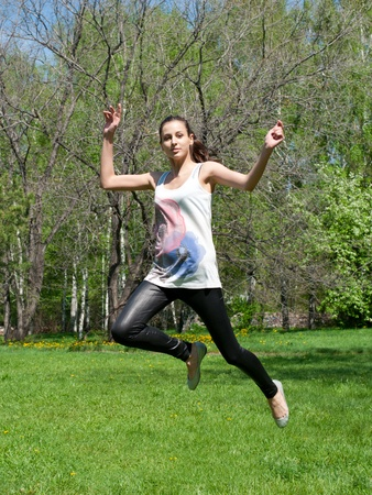 Happy young woman jumping in air with arms extended Stock Photo - 10855708