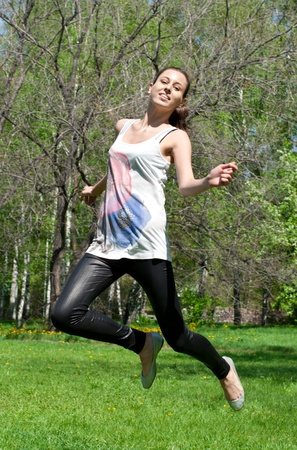 Happy young woman jumping in air with arms extended outdoors photo