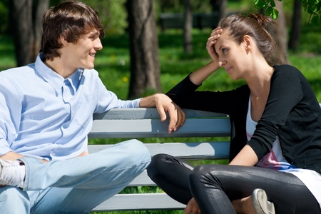 sitting on a bench: Young couple sitting together on park bench