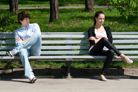 Young couple in quarrel sitting on bench in park photo