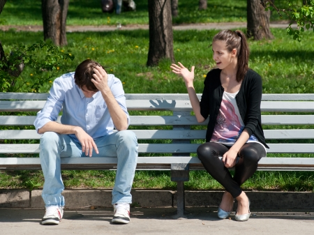 novios enojados: Pareja joven en la pelea sentado en el banco en el parque Foto de archivo