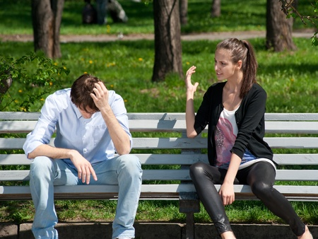 pareja enojada: Pareja joven en riña sentado en el banco en el parque
