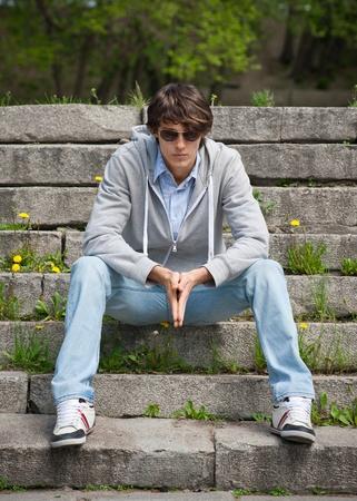 modelos hombres: Retrato de hombre joven y guapo con gafas de sol sentado en las escaleras en el parque Foto de archivo