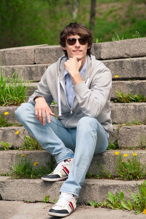 Portrait of handsome young man wearing sunglasses sitting on stairway in park Stock Photo - 10855627