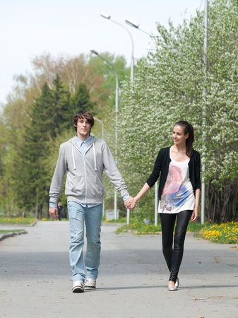 2 way: Young couple walking together hand by hand  in park