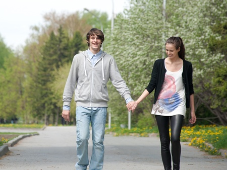 boy and girl holding hands: Young couple walking together hand by hand  in park